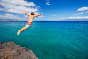 Workout Wednesday - Man jumping off cliff into the ocean. Summer fun lifestyle.