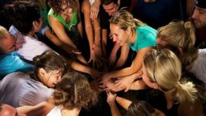 Group putting hands together in a circle.