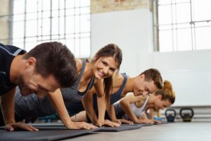 Group of young people doing pushups in a gym.