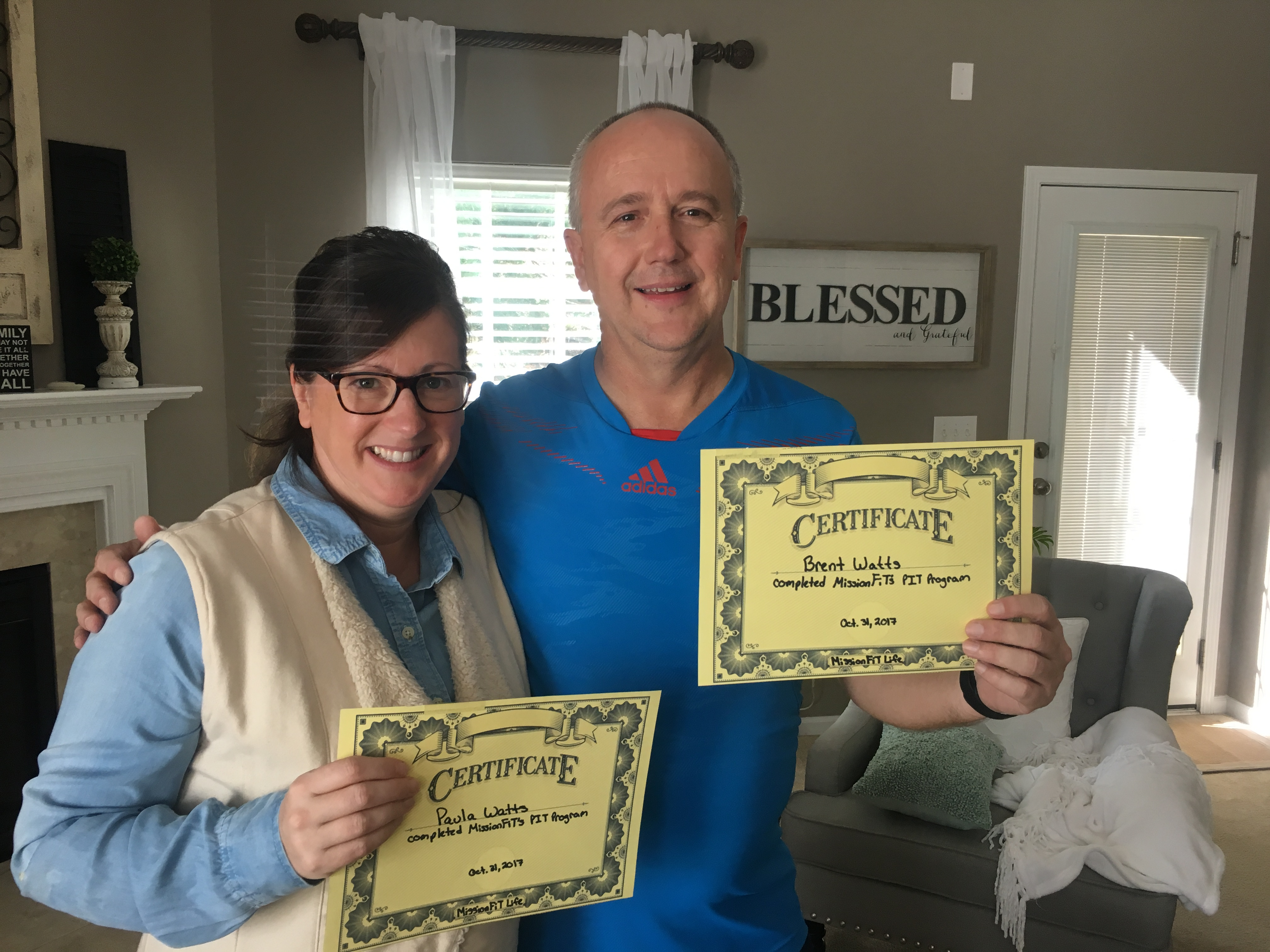 Today's Spotlight Athlete, Pastor Brent Watts, pastor brent in a blue t-shirt and Paula in a blue shirt with white vest holding their completion certificates smiling