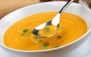 Foodie Friday - Butternut Squash Soupm a picture of a white ceramic bowl of orange butternut squash soup with a ladle in it