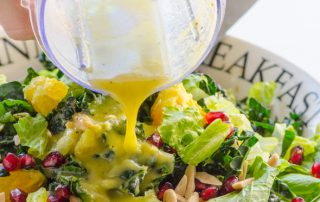Foodie Friday - Winter Salad, picture of a green salad with cranberries and a homemade dressing being poured over top