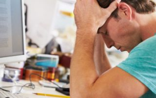 Is stress affecting your physical health, man at a desk with his head in his hands looking stressed out