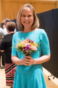 Testimony Tuesday with Joy Motte, Joy in a teal blue dress holding purple flowers