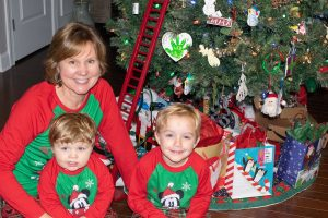 Testimony Tuesday with Joy Motte, Joy with her 2 grandkids in Christmas jammies smiling in front of the tree