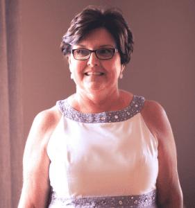 Testimonial - Kelly Morenus, Kelly smiling in a white dress