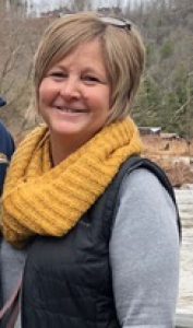 Testimony Tuesday with Sandy Morgan, headshot of Sandy smiling outside with a yellow scarf on