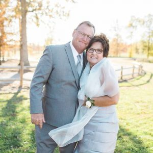 Testimonial - Kelly Morenus, Kelly smiling with her husband all dressed up at a wedding outside.
