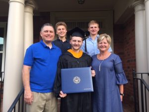 Testimony Tuesday with Sandy Morgan, Sandy in a blue dress posing with her husband and three sons after one just graduated