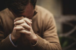 April is Stress Awareness Month, a pastor in a cream colored sweater praying looking stressed