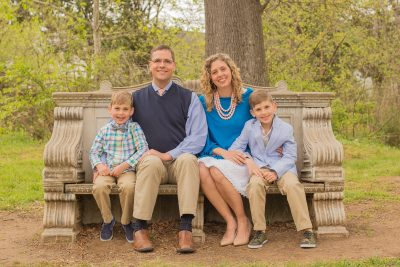 Testimony Tuesday with Emily Massey, Emily in a blue top with her family sitting on a bench